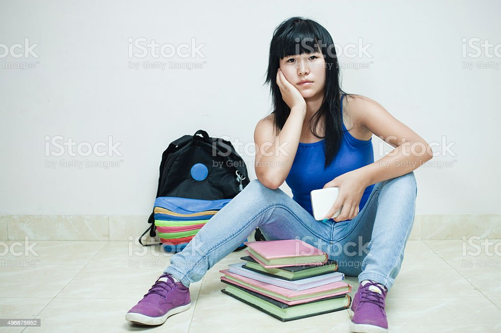 Overburdened sad Asian girl student sitting on floor with books. stock photo