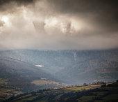 Overcast scene in cloudy mountains. Autumn rain