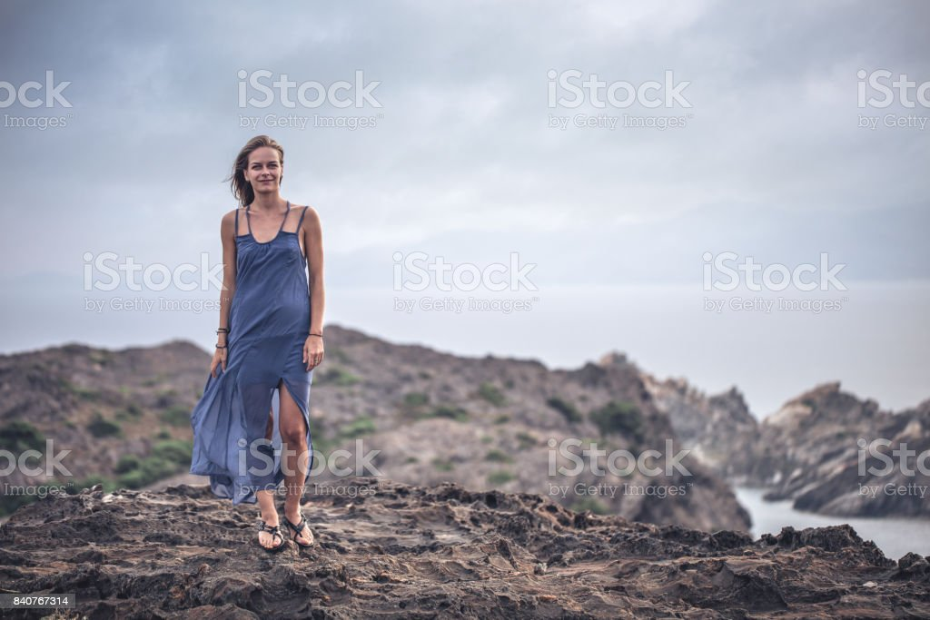 Overcast sky over lonely woman standing alone at the rocky coast stock photo