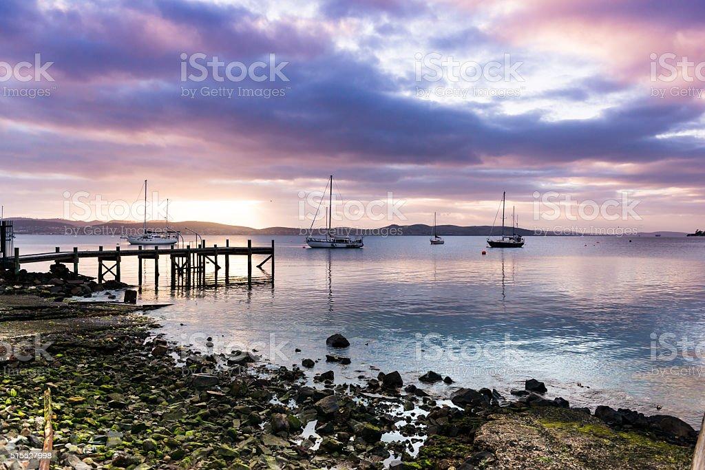 Overcast Sunrise on Derwent Estuary with Yachts and Foreground Rocks stock photo