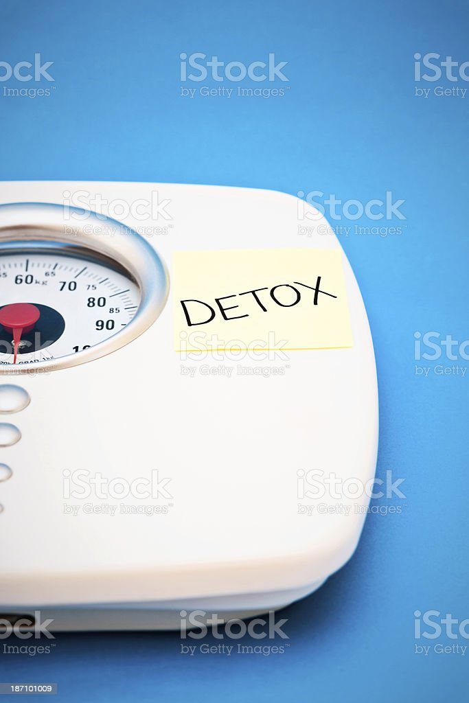 Overdone the eating and drinking? Bathroom scales recommend a Detox royalty-free stock photo