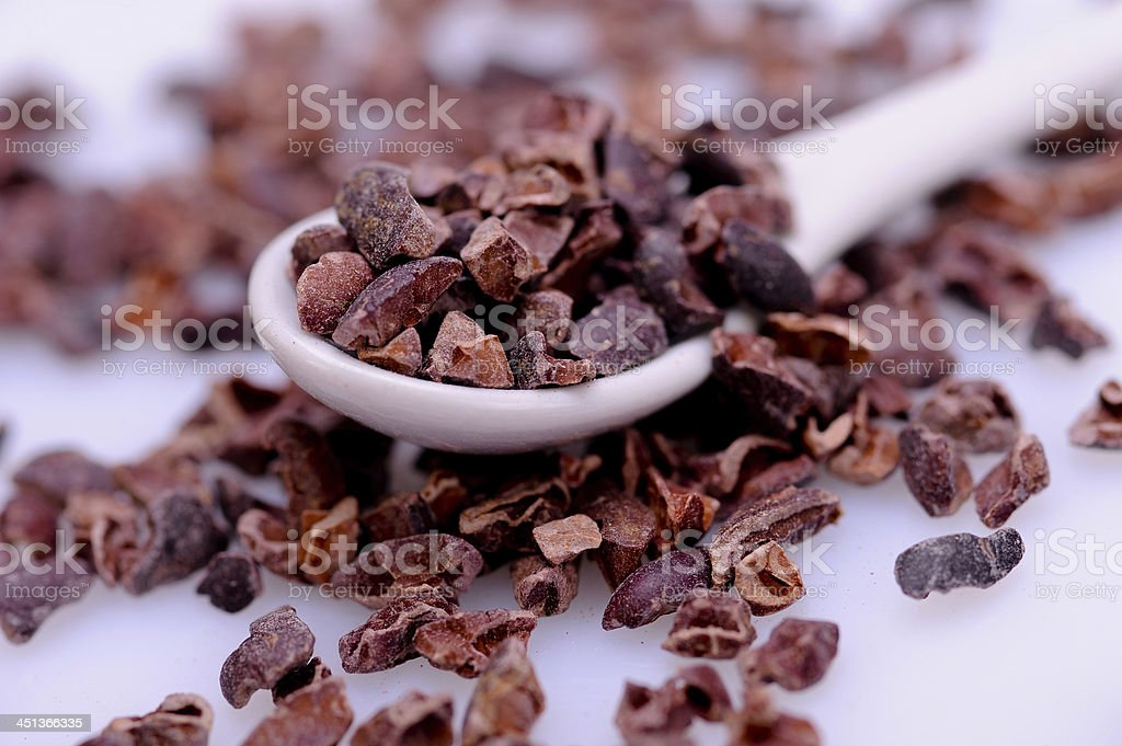 Overfilled spoon of raw organic cocoa nibs stock photo