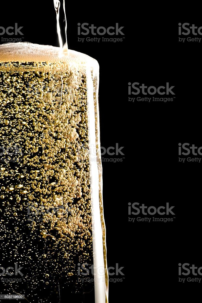 overflow pouring champagne in the flute with golden bubbles stock photo