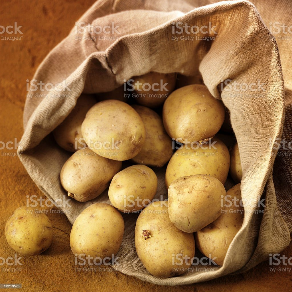 overflowing bag of potatos royalty-free stock photo