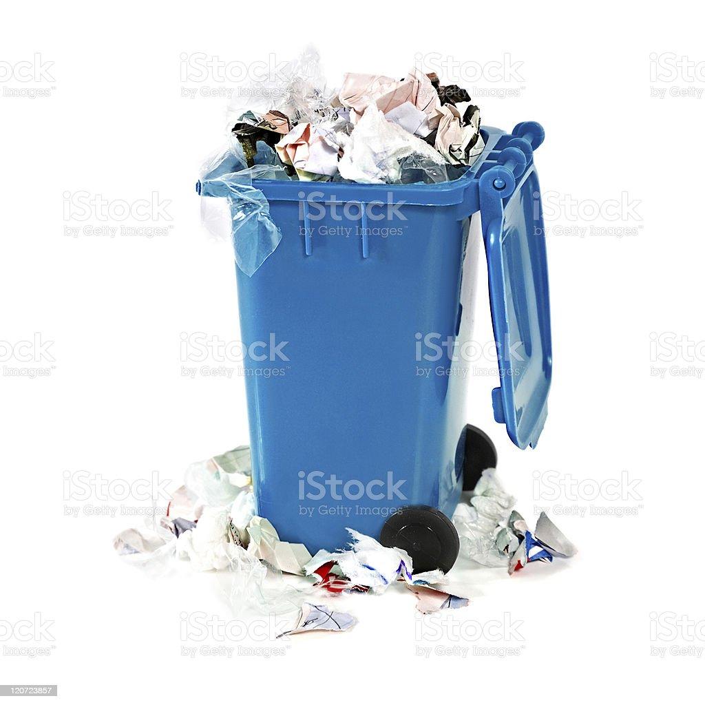 overflowing blue garbage bin stock photo
