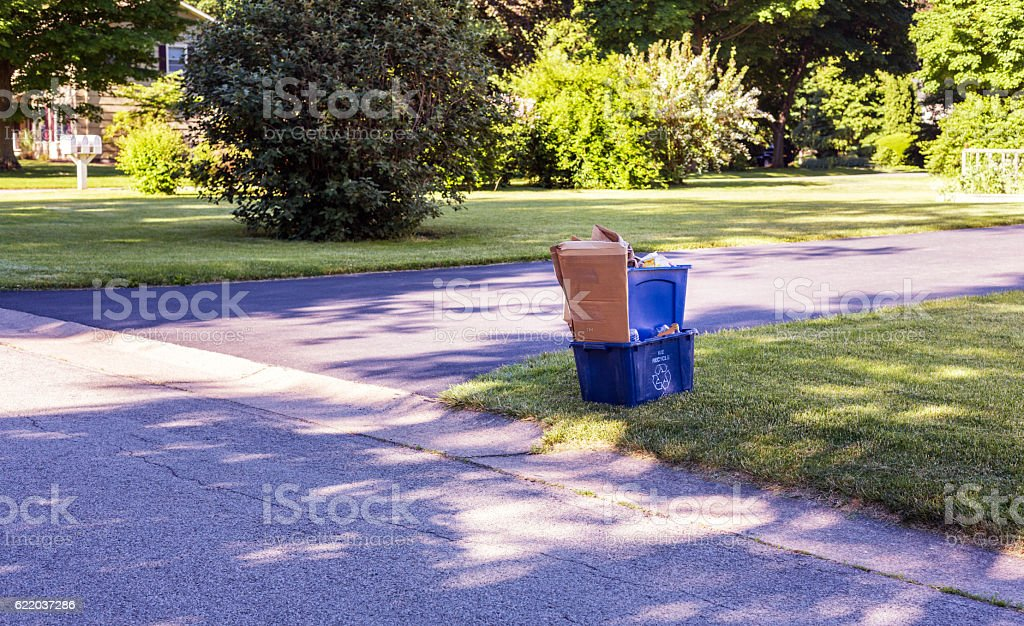 Overflowing Blue Garbage Recycling Bins at Driveway and Street Intersection stock photo