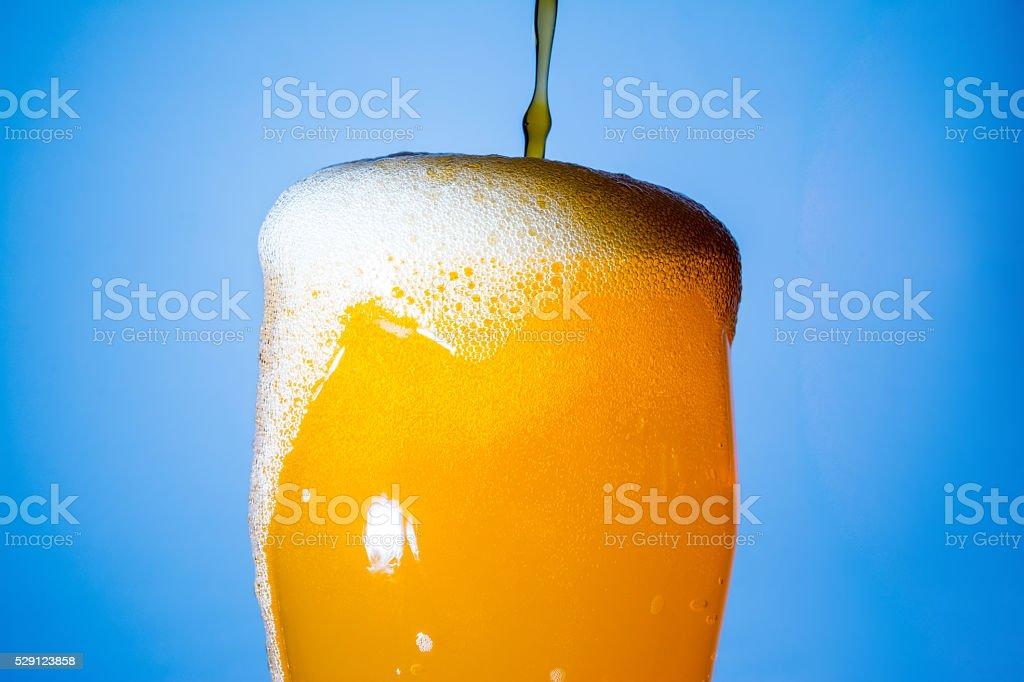 Overflowing glass of orange soda on blue background stock photo