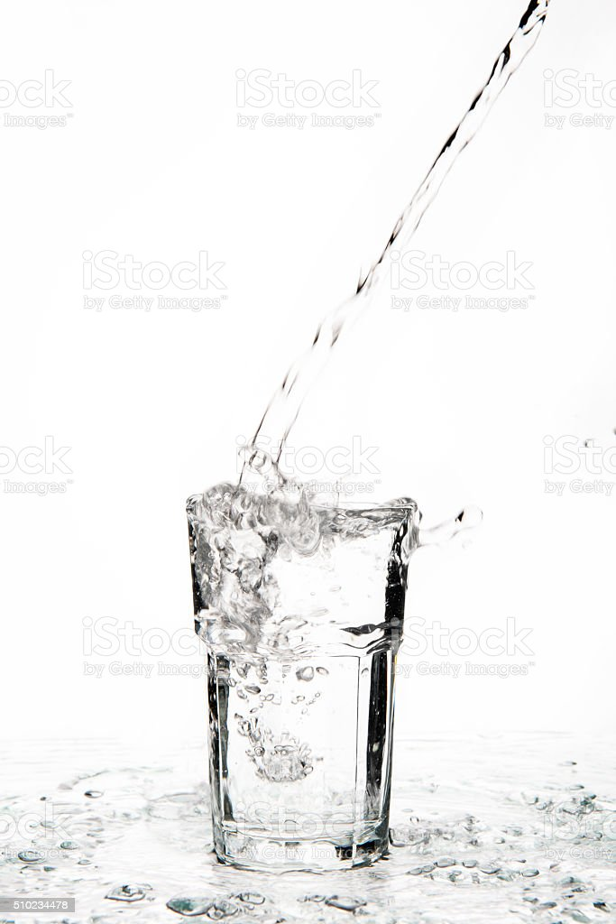 Overflowing glass of water on a glass table stock photo