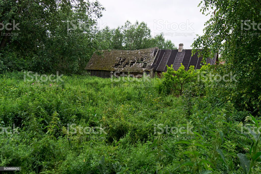 Overgrown garden and abandoned dilapidated house stock photo