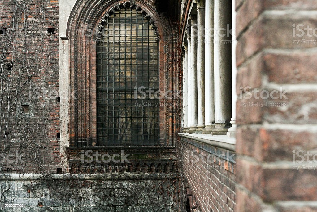 Overgrown loach brick wall with a Gothic stained-glass stock photo