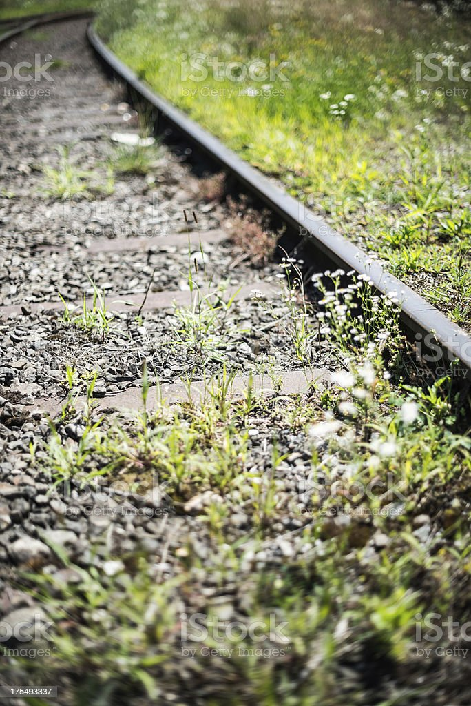 overgrown railroad track showing the end stock photo