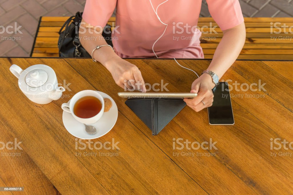 Overhead Angles of young woman checking email on digital tablet, listen to podcast and drinking tea stock photo