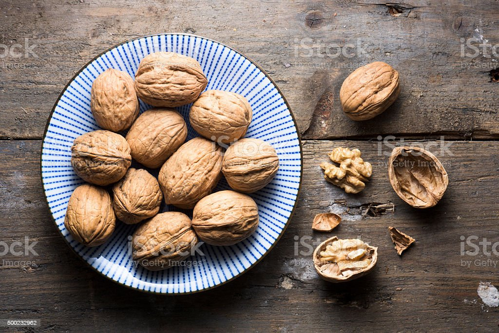 Overhead bowl of walnuts on a rough wooden background stock photo
