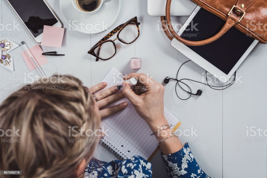 Overhead Business Angles woman at office desk painting nails stock photo