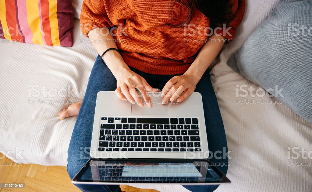 Overhead close up of a young woman working on laptop stock photo