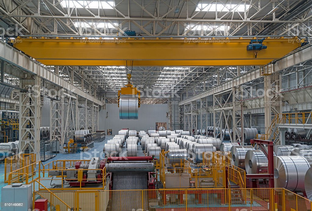Overhead crane carrying large aluminum steel rolls stock photo