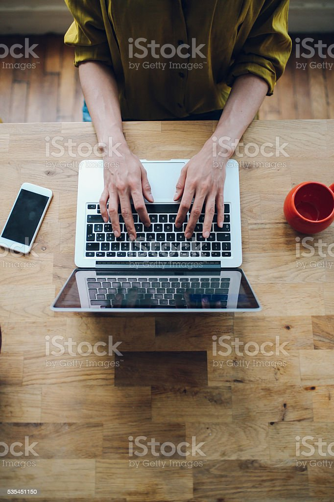 Overhead image of a female blogger writing on the laptop stock photo