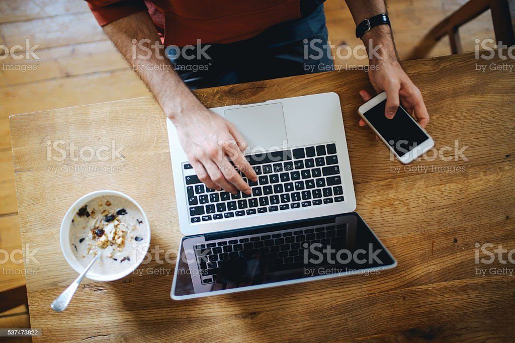 Overhead image of a man writing on the laptop stock photo
