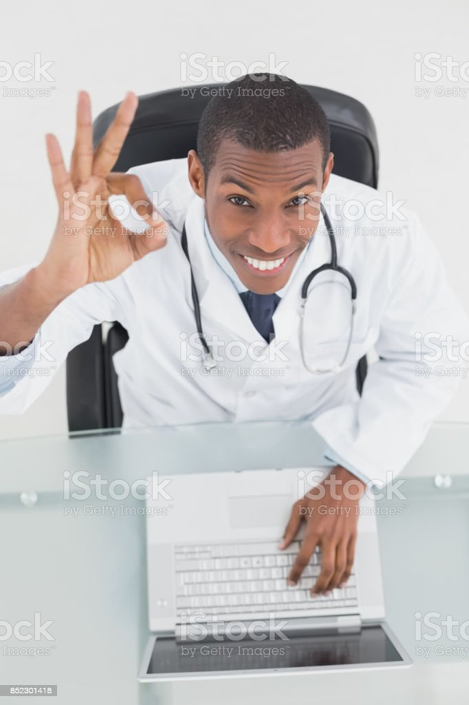 Overhead of a smiling male doctor with laptop gesturing okay sign stock photo