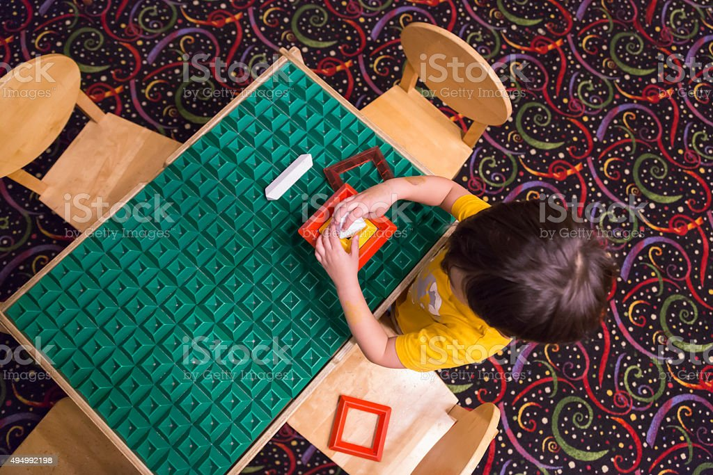Overhead of Boy Playing With His Toys at Table stock photo