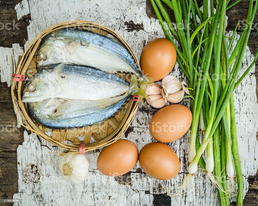 Overhead of fish in a basket next to brown eggs and herbs stock photo
