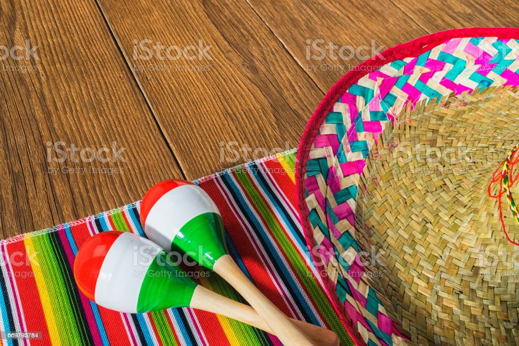 Overhead of Mexican celebration with maracas and sombrero on wood planks stock photo