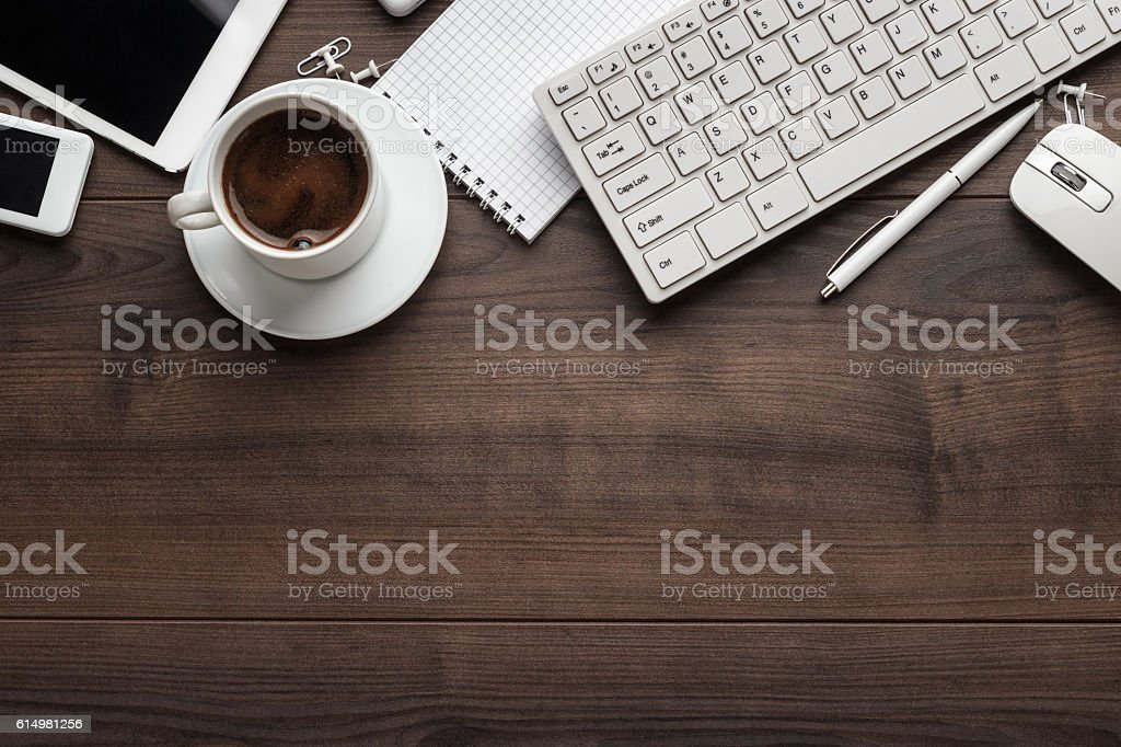 office table with notebook, computer keyboard, mouse, cup of coffee,...