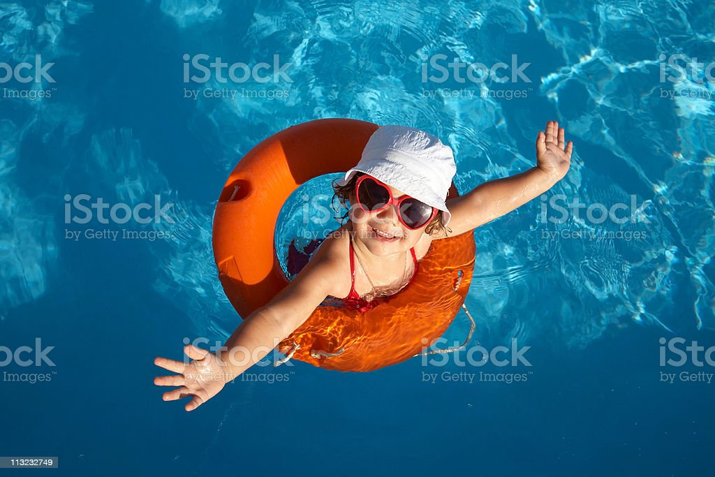 Overhead of young girl in orange life preserver stock photo