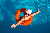 Overhead of young girl in orange life preserver