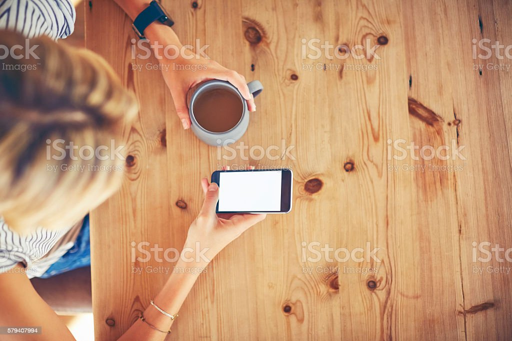 Overhead of young woman using smart phone at wooden table stock photo