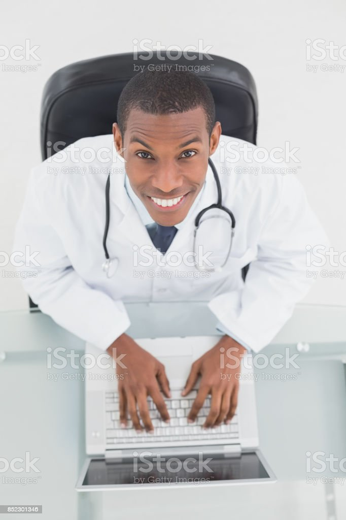 Overhead portrait of a smiling male doctor using laptop stock photo