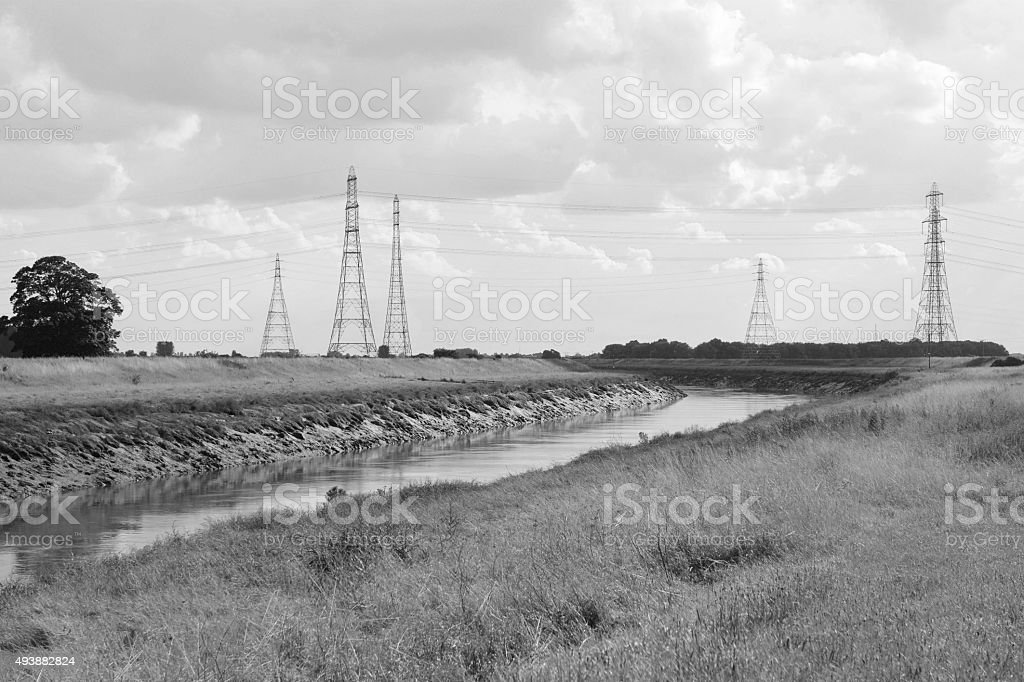Overhead power lines span the River Nene in Cambridgeshire stock photo