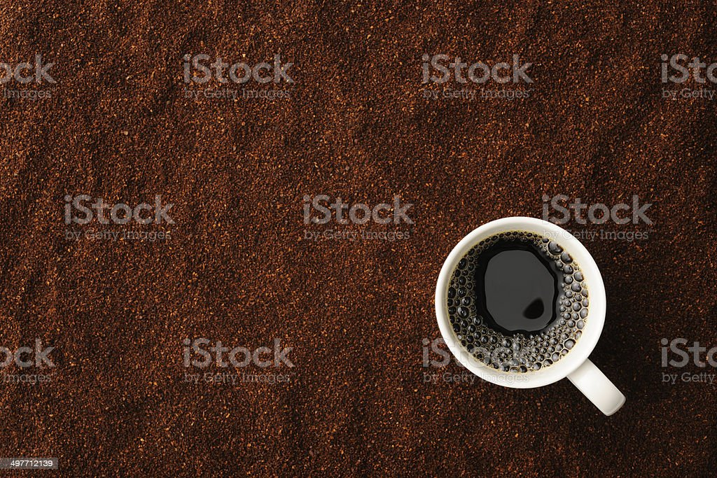 Overhead shot of a cup of coffee on coffee beans royalty-free stock photo