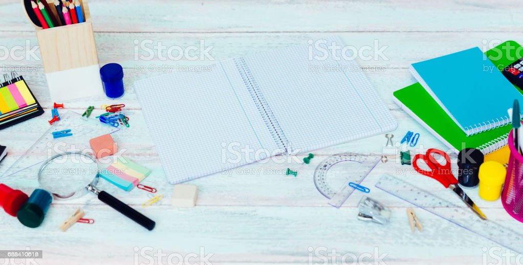 Overhead shot of an opened school exercise book. surrounded by stationery items on a light wood desk. stock photo