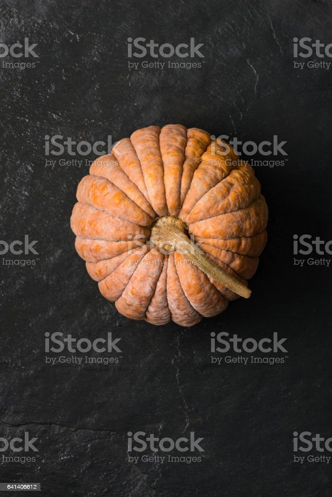 Overhead Shot of Cinderella Squash on Dark Gray Stone Surface stock photo