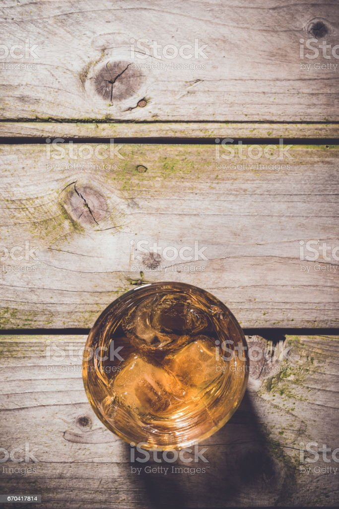 Overhead shot of glass of whiskey on wooden table stock photo