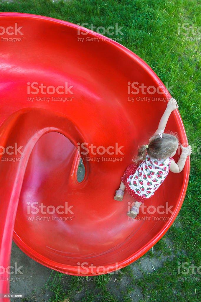Overhead shot of little blonde girl sliding down playground slide stock photo