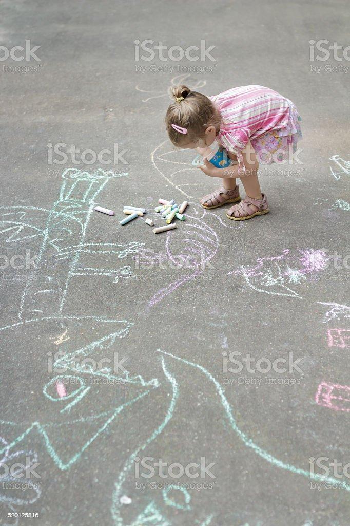 Overhead shot of little Caucasian girl chalking on yard stock photo