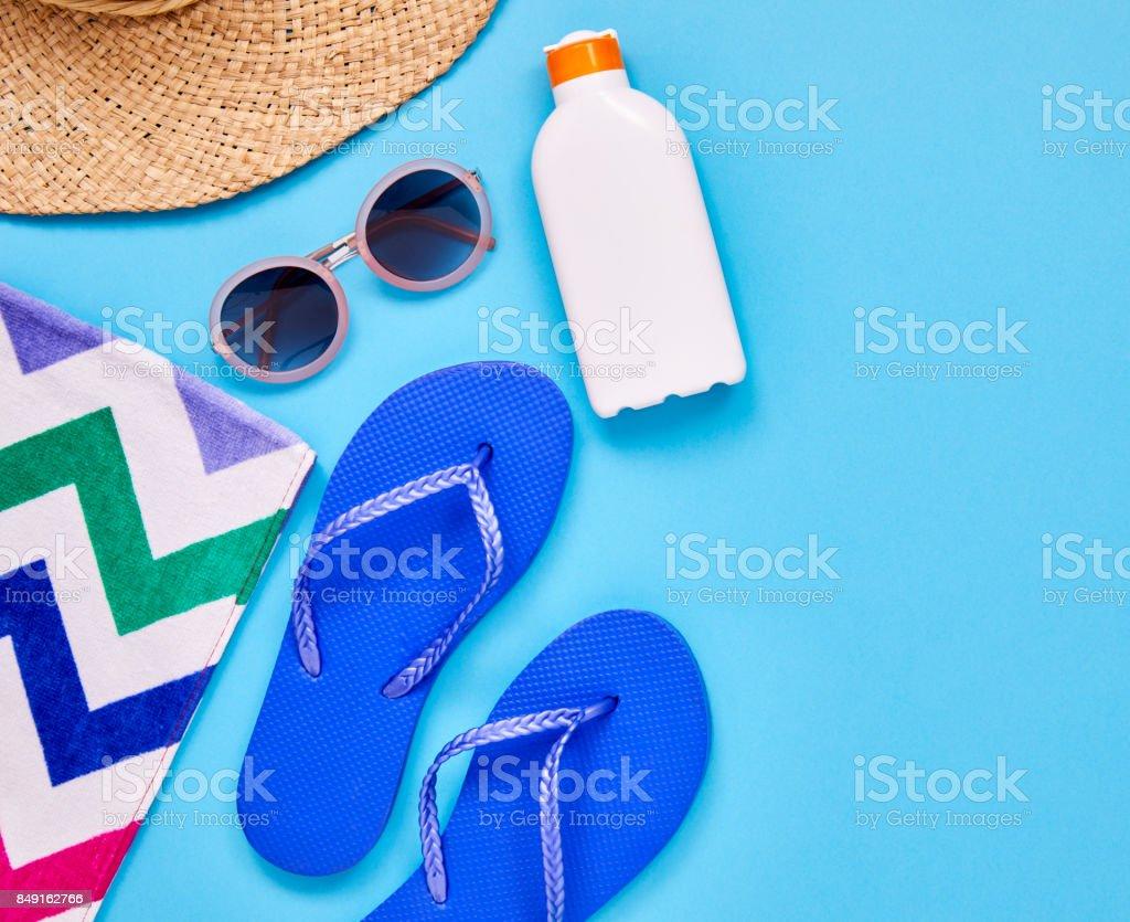 Overhead shot of flip-flop sunglasses suntan lotion sun hat and beach...