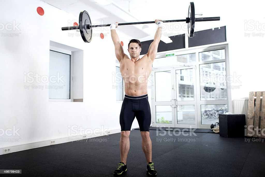 Overhead squat, push press with barbell stock photo