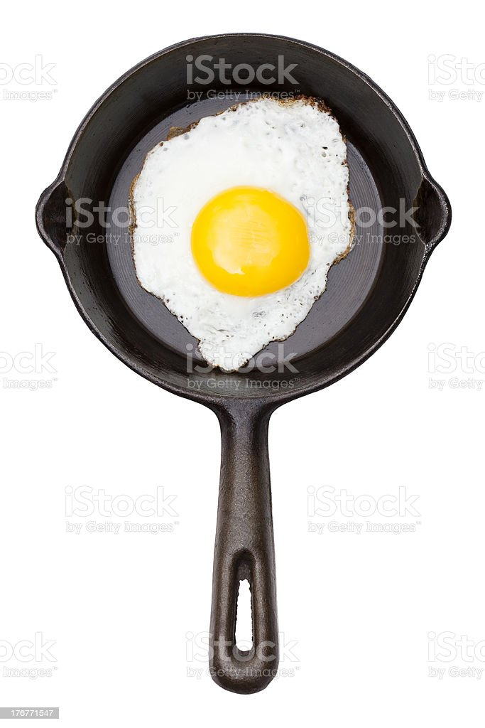 Overhead view fried egg cast iron skillet white background stock photo