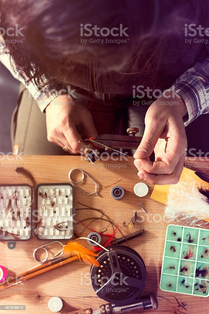 Overhead View Of a Fly Fisherman Tying Flies For Fishing stock photo