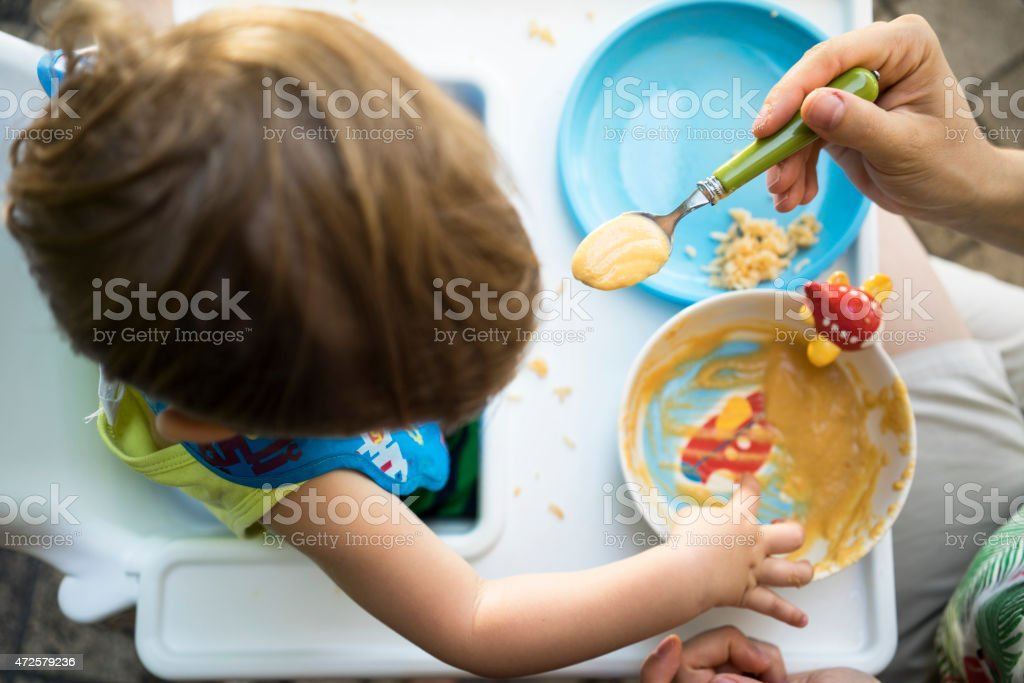 Overhead view of a mother spoon-feeding a child on highchair stock photo