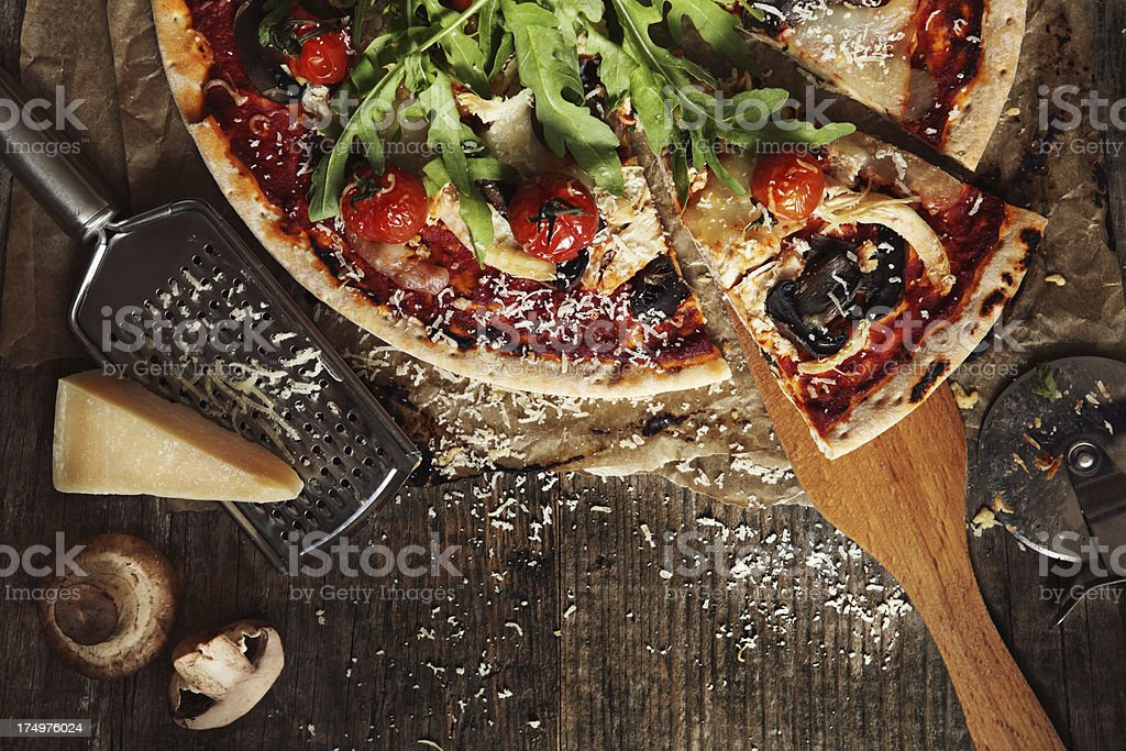 Overhead view of a pizza and ingredients on table stock photo