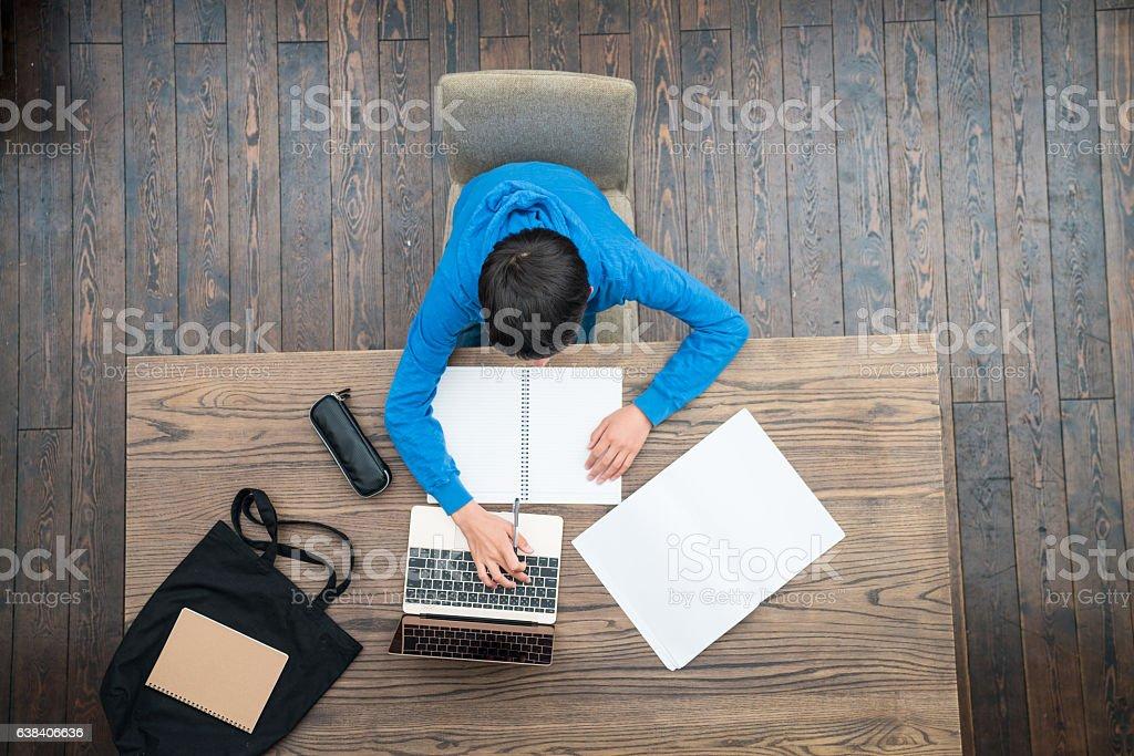 Overhead view of a teenage boy doing homework stock photo