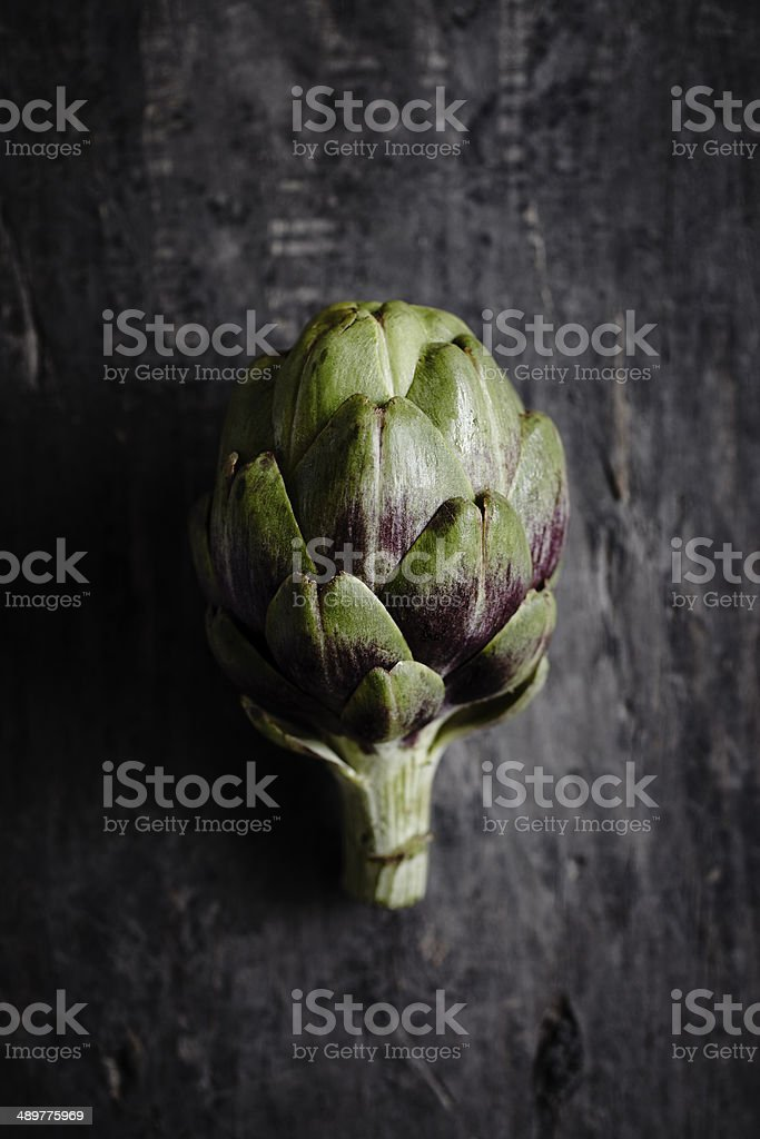 Overhead view of an organic artichoke on dark wooden table. stock photo
