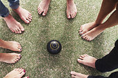 Overhead view of bare feet friends around lawn bowls