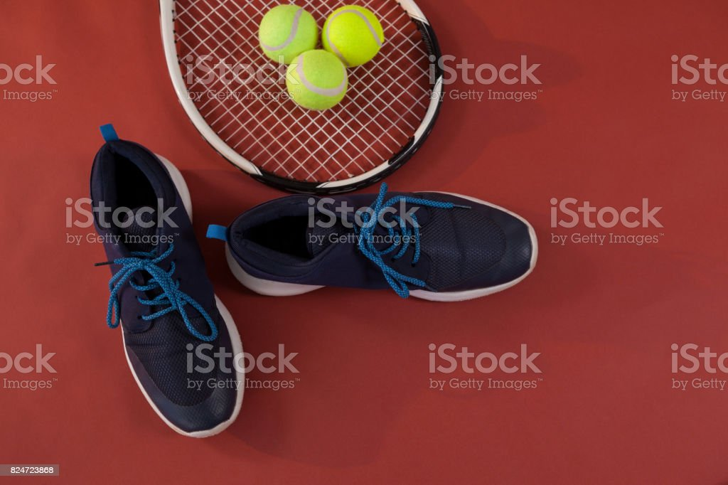 Overhead view of blue sports shoes by tennis racket and balls on...