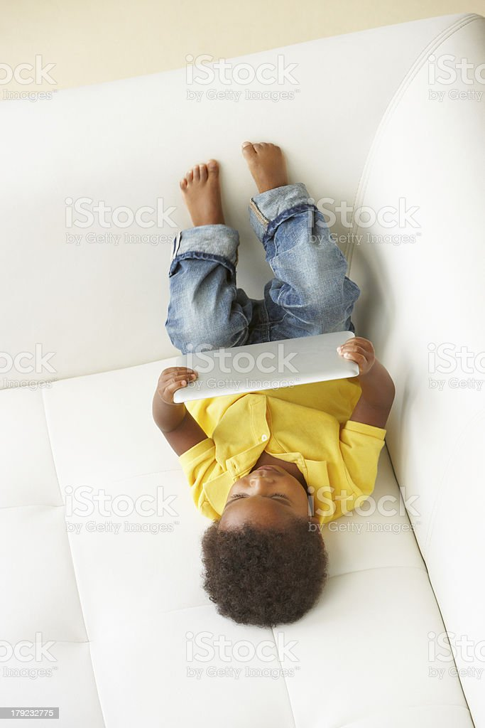 Overhead View Of Boy On Sofa Playing With Digital Tablet royalty-free stock photo