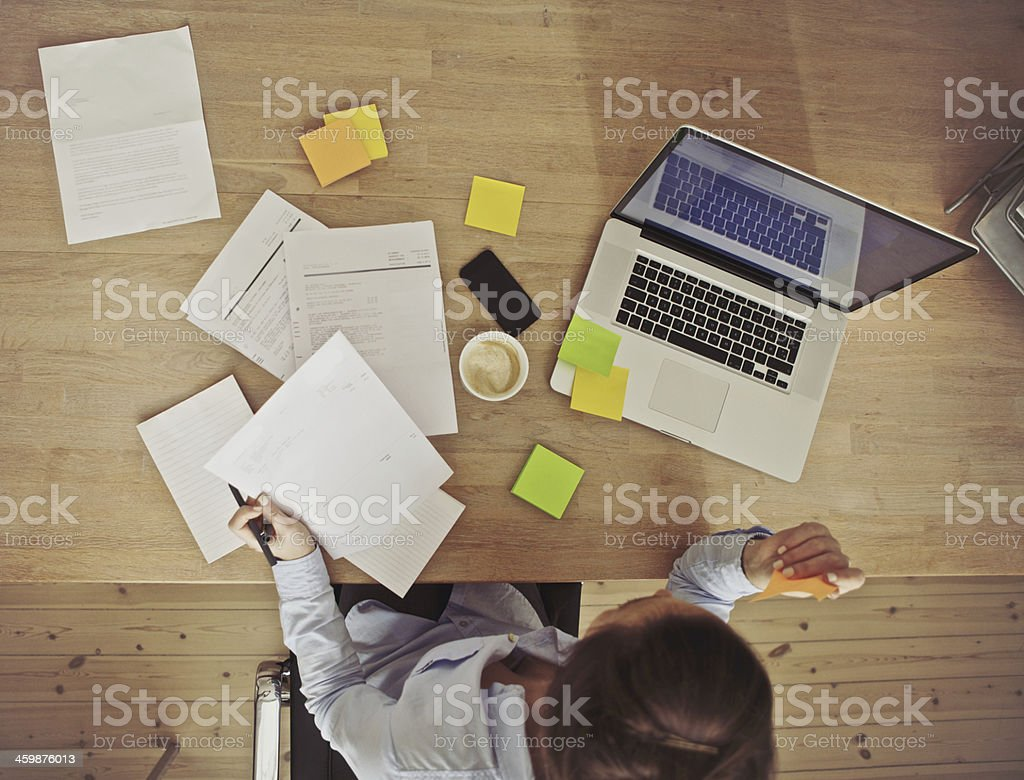 Overhead view of businesswoman working at desk stock photo